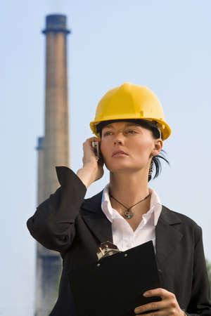 lluvia acida: Una bella mujer de cabello oscuro que llevaba un gorro duro y hablando por su tel�fono m�vil mientras est� frente a una f�brica y sus chimeneas