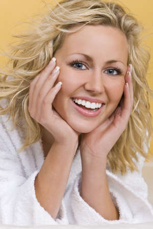 restful: Studio shot beautiful young blond woman wearing a bathrobe looking restful and happy