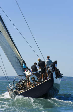 sail boat: A fully crewed racing yacht catching the wind Stock Photo