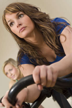A beautiful young brunette woman on an exercise bike/spinning bike at the gym Stock Photo - 2827500