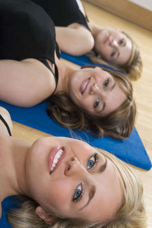 Three beautiful young women laying down on mats at a fitness class Stock Photo - 2834211