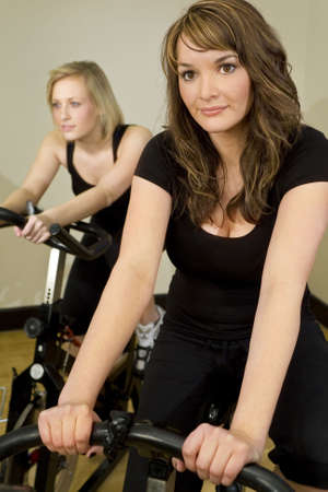 Two beautiful young women on exercise bikes/spinning bikes at the gym Stock Photo - 2861946