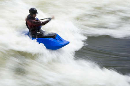 kayaker: A slow shutterspeed shot of a kayaker in very rough whitewater. Shot with copyspace on the right hand side of the frame. Stock Photo