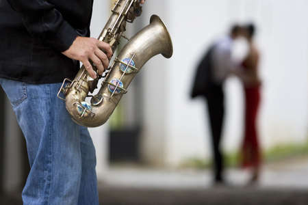 A street musician plays his saxophone while a  couple can be seen out of focus in the background photo