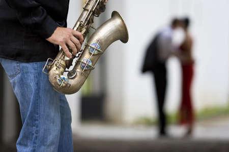 serenata: Un m�sico toca su saxof�n, mientras que una rom�ntica pareja puede verse fuera de foco en el fondo