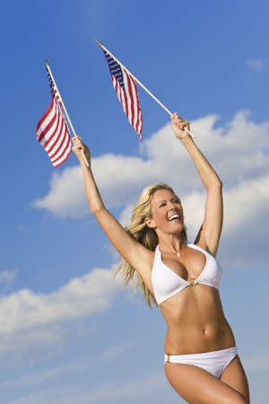 american sexy: A stunningly beautiful young woman in a white bikini holds two stars and stripes flags above her head