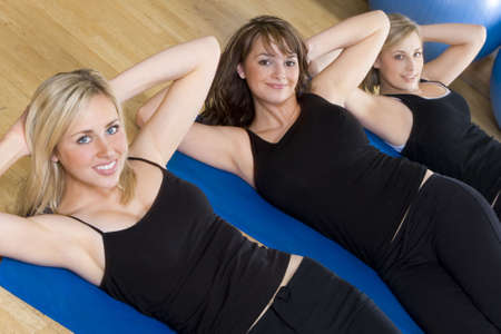 Three beautiful young women working out at the gym, the focus is on the brunette girl in the centre photo