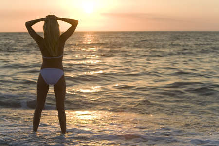 A beautiful bikini clad blond stands in the surf at sunset Stock Photo - 2925323