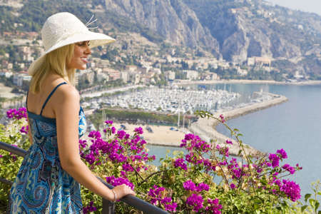 menton: A beautiful young woman overlooking Menton harbor on the Mediterranean coast of France Stock Photo