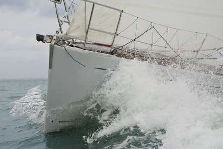bow of boat: Close up on the bow of a sailing yacht breaking through a wave