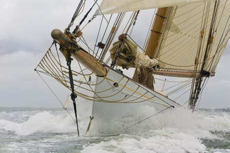 hull: Close up on the bow of a classic sailboat breaking through a wave