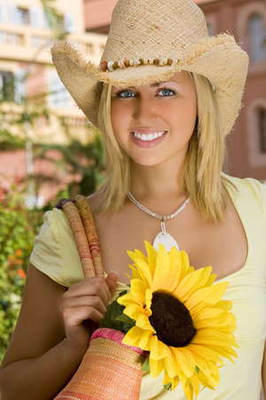 sunhat: A beautiful young blond woman wearing a straw cowboy hat carrying a shopping bag of sunflowers