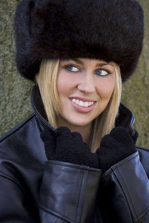 A beautiful young blond woman wearing a (fake) fur hat, leather jacket and gloves