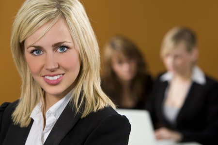 An attractive young female executive in focus in the foreground while her colleagues work on a laptop behind her photo