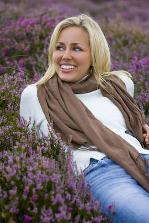 blonde blue eyes: A beautiful blond haired blue eyed young woman laying amongst flowering heather and laughing