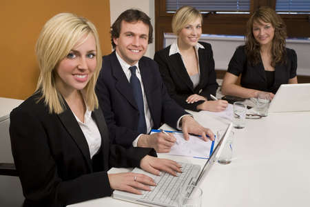 Three female executives and one male having a meeting in a boardroom - the focus is on the blond businesswoman in the foreground. photo