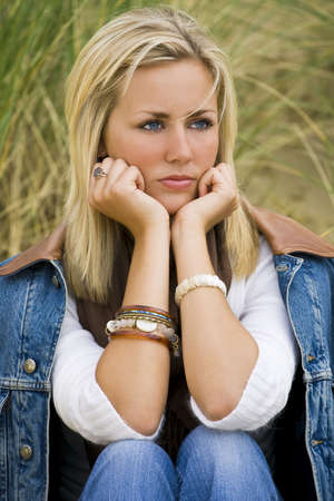 blonde close up: A beautiful blond haired blue eyed model sits thinking amid tall green grass