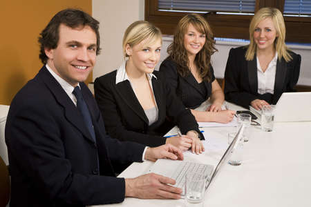 Three female executives and one male having a meeting in a boardroom - the focus is on the businessman in the foreground. photo