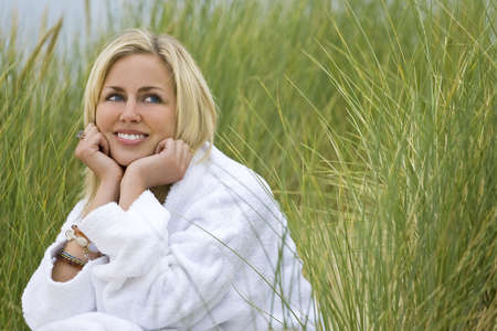 toweling: A beautiful blond haired blue eyed model wearing a white toweling robe sits amid tall grass Stock Photo