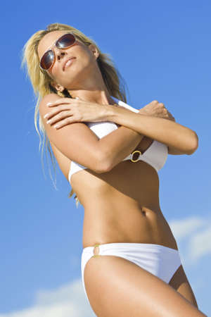 A beautiful young blond woman wearing a white bikini and sunglasses shot against a blue sky