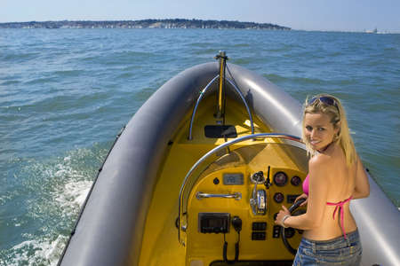 A beautiful young woman driving her powerboat around a mediterranean coastline filled with sailing boats