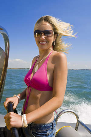 A beautiful young woman driving her powerboat at speed around a mediterranean coastline Stock Photo