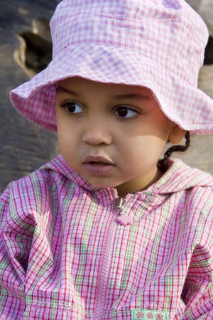 chequer: A beautiful little mixed race girl dresses in pink plaid patterns