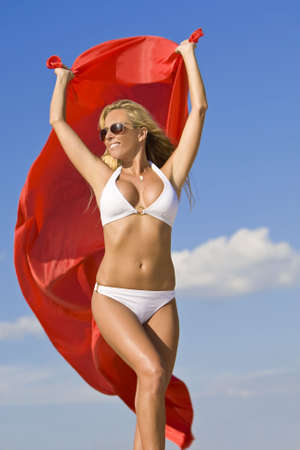 A beautiful young blond woman wearing a white bikini and sunglasses with red material blowing in the wind shot against a blue summer sky