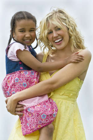 A beautiful blond haired blue eyed young woman having fun with a mixed race young girl  photo