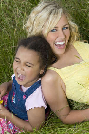 A beautiful blond haired blue eyed young woman having fun with a mixed race young girl in a field of long grass photo