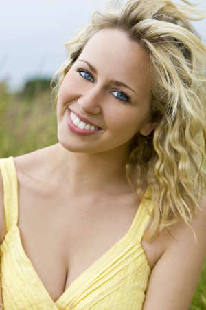A beautiful blond haired blue eyed model wearing a yellow dress sits amid tall grass Stock Photo - 3203575