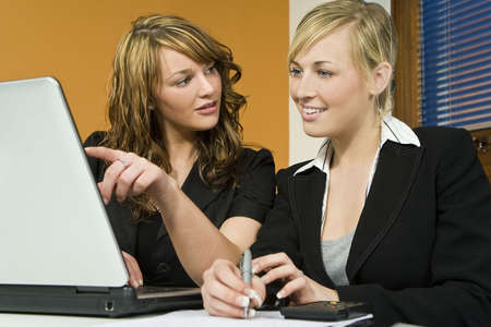 Two attractive young female executives working together on a laptop photo