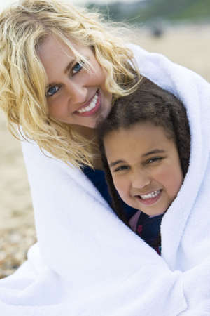 herself: A beautiful blond haired blue eyed young woman keeping herself and her young daughter warm in a towel at the beach Stock Photo