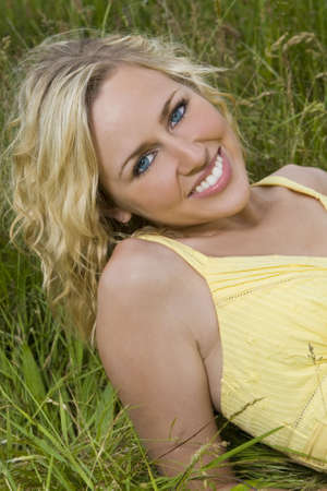 A beautiful blond haired blue eyed model laying down amid tall grass Stock Photo - 3259241