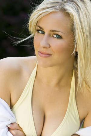 blonde yeux bleus: Une belle blonde aux yeux bleu cheveux mod�le portant un bikini et chemise blanche abattu devant en utilisant la lumi�re naturelle