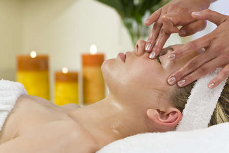 facial treatment: A young woman relaxing at a health spa while having a facial treatment Stock Photo