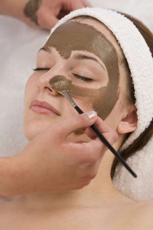 masajes faciales: Una hermosa mujer joven morena de chocolate con una m�scara facial aplicada por una est�tica  Foto de archivo