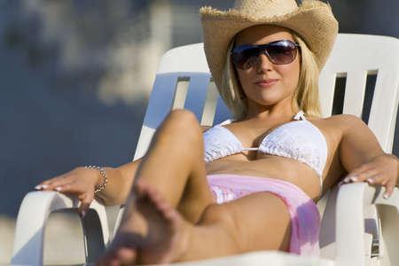 cappello cowboy: Una bella giovane donna bionda in occhiali da sole e cappello da cowboy rilassa al sole in riva al mare Archivio Fotografico