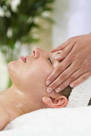 facial massage: A young woman relaxing at a health spa while having a facial treatment Stock Photo