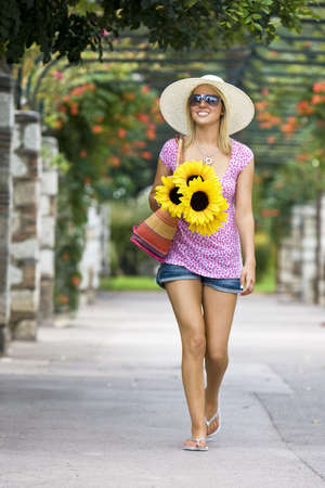 tanned: A beautiful young woman waalking through a flower covered walkway carrying a basket of sunflowers