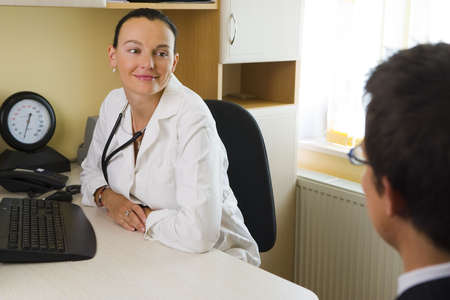 blood pressure monitor: An attractive female doctor listening to a male patient, with a blood pressure monitor beside her Stock Photo