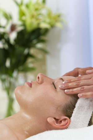 A young woman relaxing at a health spa while having a facial treatment Stock Photo