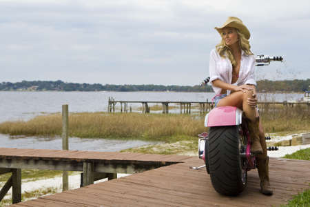 A classic shot of an American blond sitting on a chopper looking out over a lake