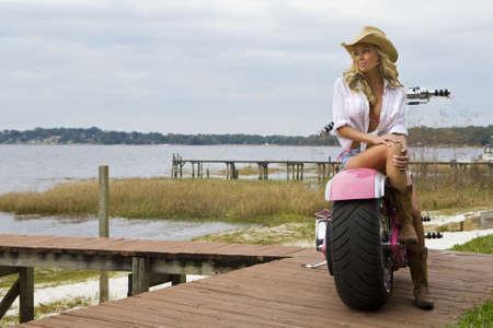 motorrad frau: Ein klassischer Schuss eines amerikanischen blond sitzt auf einem Chopper mit Blick auf einen See  Lizenzfreie Bilder