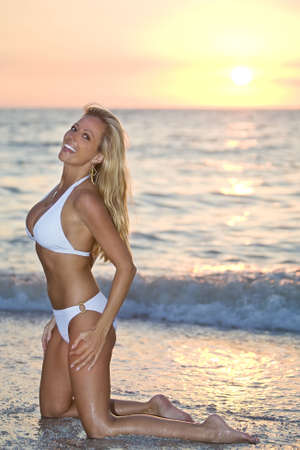 A beautiful bikini clad blond kneeling in the surf at sunset Stock Photo - 3459067