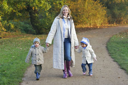 A mother, her son and daughter walking through a park filled with autumnal colors photo