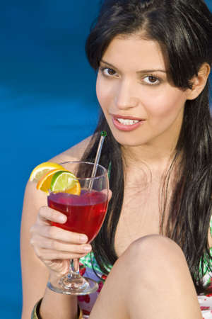 A beuatiful young Hispanic woman enjoying a cocktail by her swimming pool photo