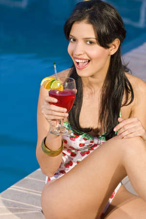 A beautiful young Hispanic woman drinking a cocktail with a swimming pool in the background Stock Photo - 3484295
