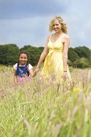 A beautiful blond haired blue eyed young woman having fun walking through a field with a mixed race young girl in a field of long grass photo