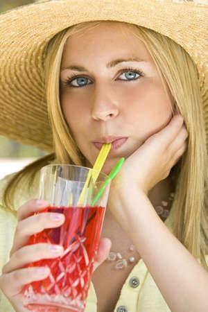 A beautiful young woman in a sun hat enjoying a long cool drink photo